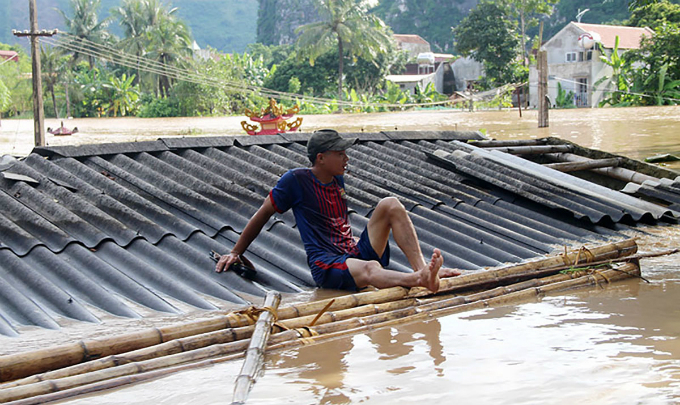 A man sits on a houses submerged roof after a sleepless night of escaping with floods.