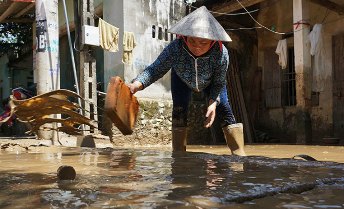 A woman gets back to her home and clean up mud left by flash floods.