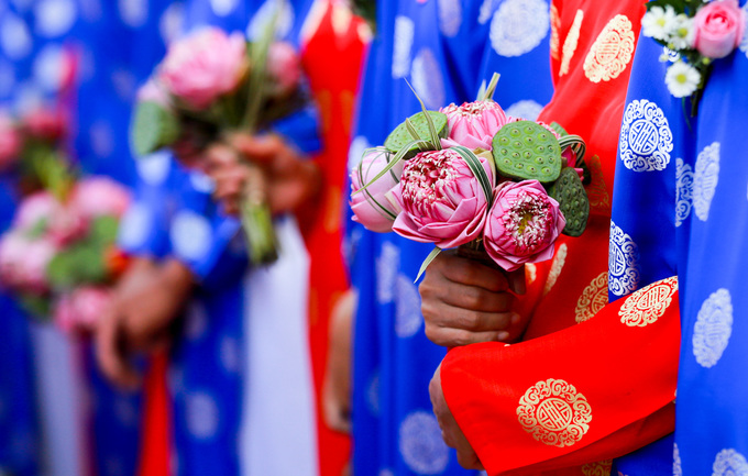 The group wedding is held for couples with limited financial income and difficult living conditions. The happy couples held bouquets of lotus flowers as they lined up to get married, offically.