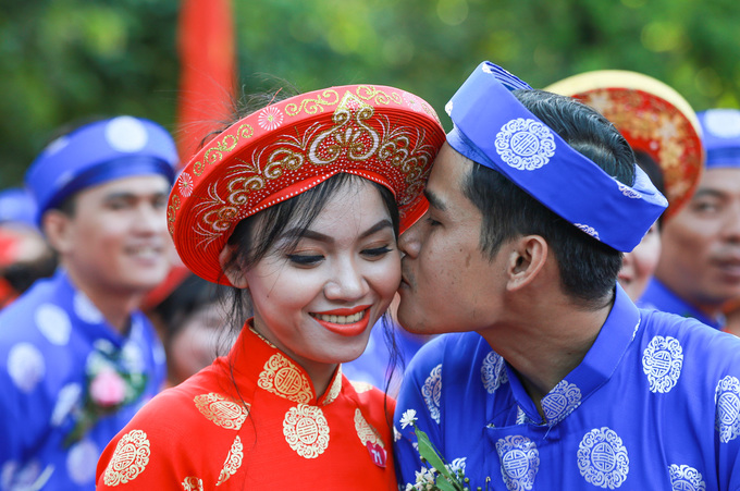 Duy Nhat, 36, places a kiss on the cheek of his similing bride, Van Anh, 24. Life as a worker is hard, I keep working overtime, but the salary is just enough to make ends meet. We have been dating for three years but we did not think of getting married. Now that I see my wife wear make-up and be a beautiful bride, I am so happy, said the emotional groom.