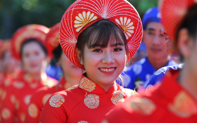 Hua Ngoc Dao, 26, looks radiant in her red traditional costume. The group wedding is unique and saves us a lot of expenses, she said.