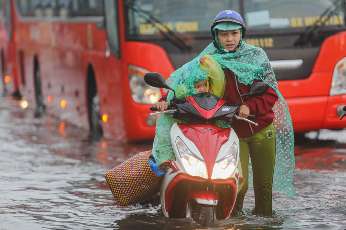Nhu and her child make their way along a flooded street.