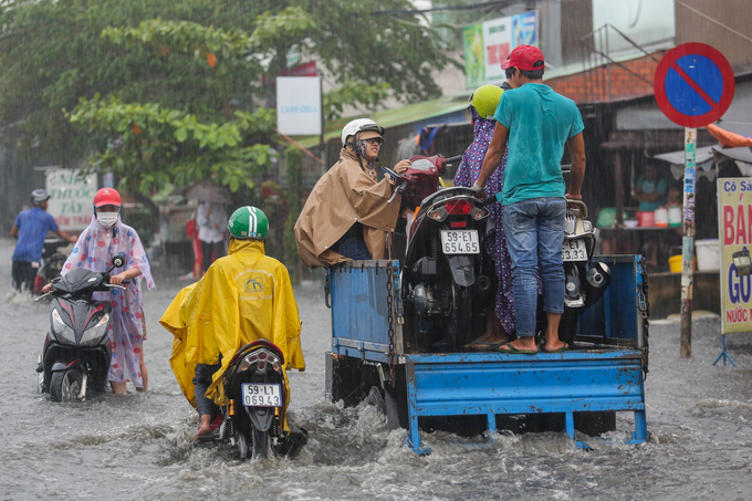 A truck carries two motorbikes and three people on the Ho Hoc Lam Road. The motorbikes engines are shutdown due to the rainwater.