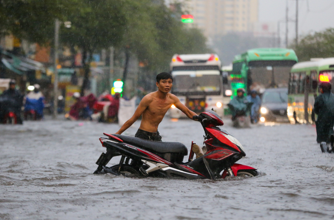 A man and a motorbike brave the flooded street on their own.