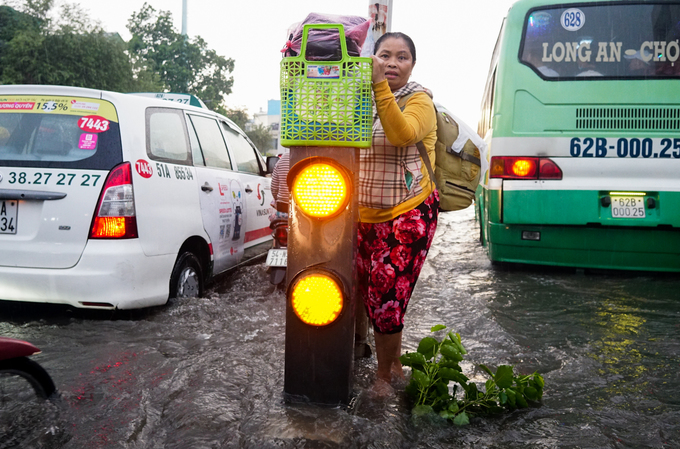 A woman holds on to a rail to avoid vehicles splashing onto her as they make their way through the flooded Hong Bang Road.