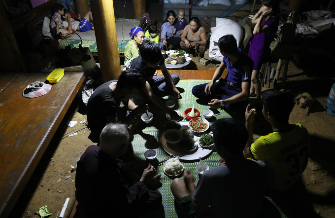 Locals have dinner under the dimmed light generated from a battery. Luong Minhs authorities said they are having headache looking ways to resettle the residents as the terrain in the commune is mountainous.