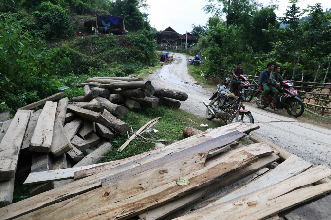 Locals save pieces of wood collected along the river bank after the  flood has gone and are now waiting for a decision on resettlement from  the authorities.