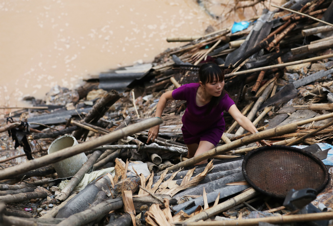Luong Thi Thai picks anything that can still be useful after her house has collapsed. The floods caught us off guard. I just had enough time to take some clothes before taking my mother and daughter to the hill. The entire house was washed away, she says.