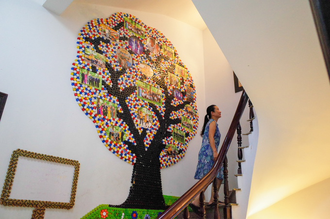 He repurposes colorful plastic cabs as a family tree decoration where he places his family photos.
