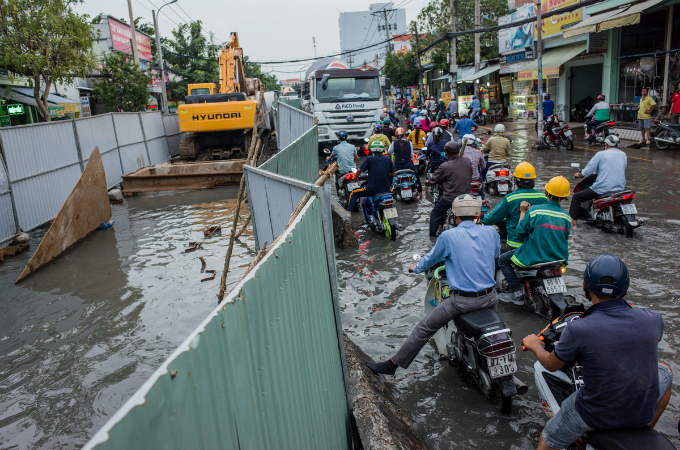 The floods send Huynh Tan Phat 30-50 centimeters under water and slow down traffic flow. And due to a construction site on the street, traffic jam lasts for around 1 km.