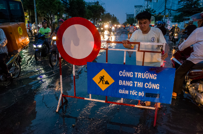 Some locals have to use signboard of the construction site to warn  drivers about the downgraded street. Due to the floods, weve been  taking turn to stay here to help those in need. We really hope that the  authorities will quickly upgrade this section, Tran Huu Nghia, a local,  says. HCMC is still in the rainy and high tide season. And as forecast  by the Southern Regional Hydrometeorological Center the tide will keep  rising in coming days