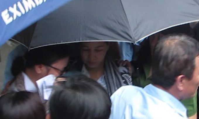 Two Eximbank employees Ho Thi Thuy and Nguyen Thi Thi are covered under umbrellas as they are escorted by police out of their office in Ho Chi Minh City in March 2018. Photo by VnExpress