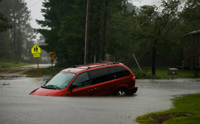 An abandoned minivan sits on a flooded road near New Bern, North Carolina