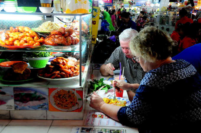 Foreign tourists enjoy Vietnamese dishes at a food stall in Ben Thanh Market. Photo by VnExpress