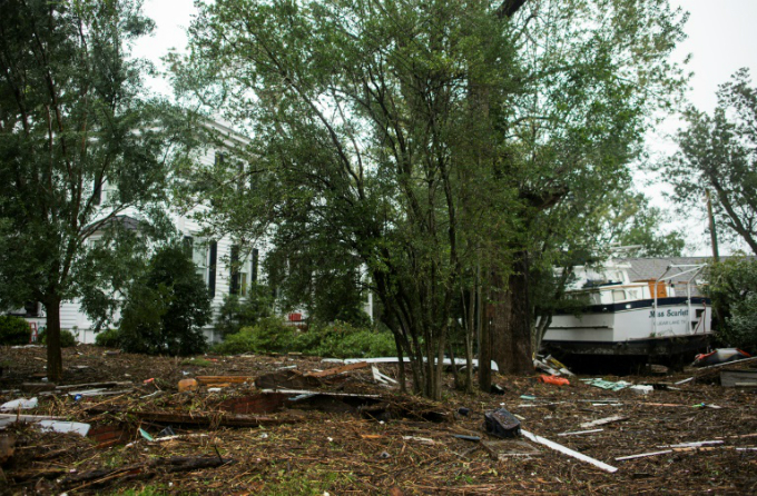 A boat sits among debris in the front lawn of a house in New Bern, North Carolina.