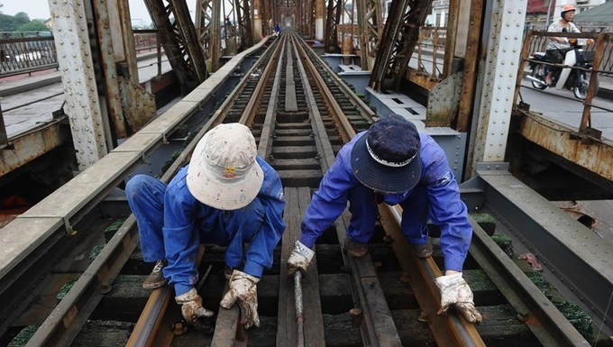 Railway workers do maintenance work on rail tracks on Long Bien Bridge in Hanoi. Photo by AFP