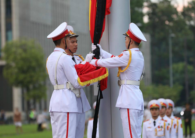 Soldiers tie a band of black cloth to the national flag as Vietnam enters two-day state mourning for President Tran Dai Quang Wednesday morning.