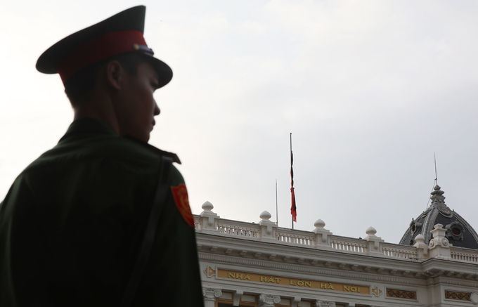 A police officer stands guard, with a flag flying at half mast in the distance on the roof of Hanoi Opera House.