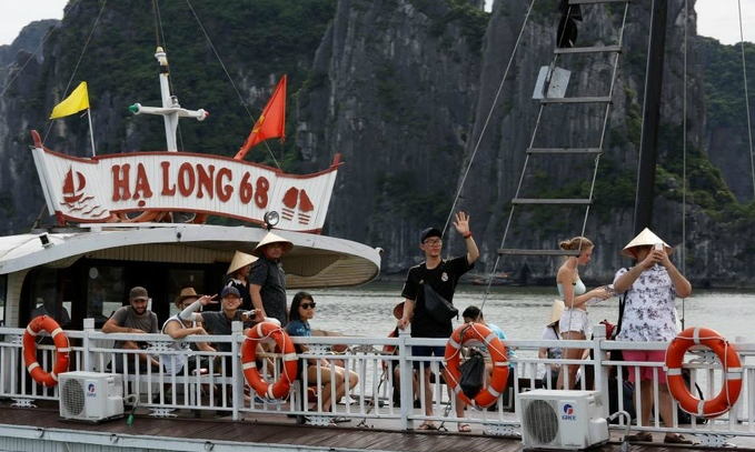 Chinese tourists are seen with others onboard during their visit in UNESCOs world heritage Ha Long Bay. Photo by Reuters/Kham