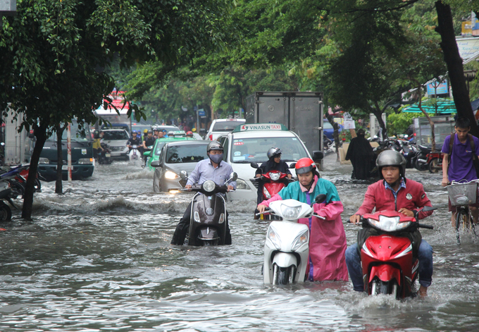 Vehicles struggle to get through the flooded street.