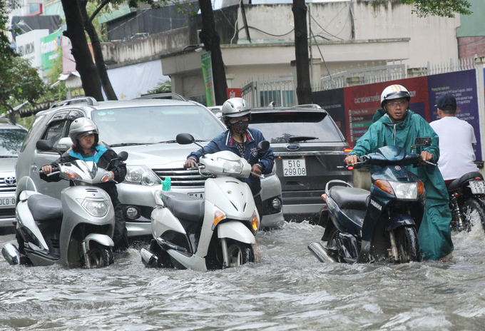 [Caption] Cars and motorbikes march on despite high levels of water getting in their way.