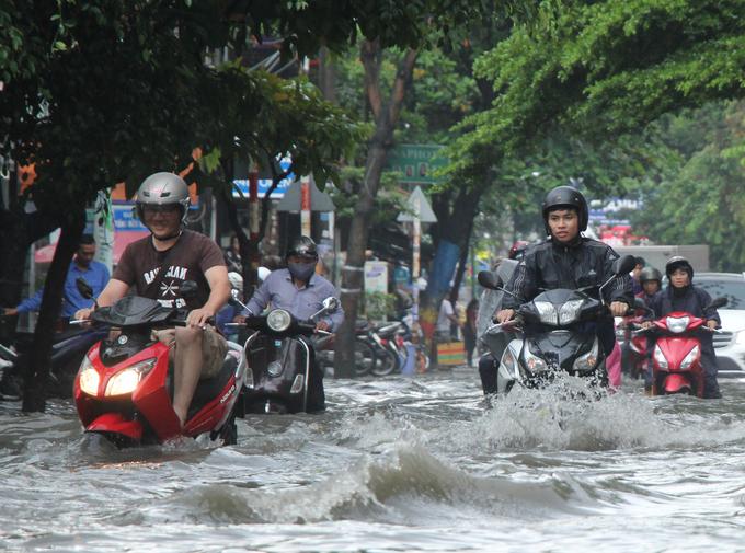 [Caption] Motorbikes splash waves on the Quoc Huong Road in District 2