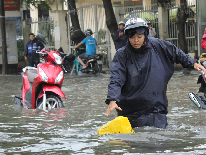 [Caption] A woman wades through the water to get her stuffs