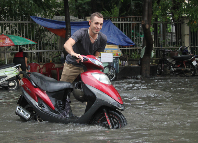 [Caption] An expat smiles as he walks his motorbike through the flooded road