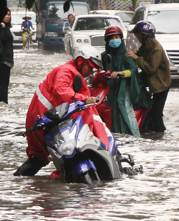 [Caption] Quynh tries to have his motorbike stands upright amidst the flooded street.