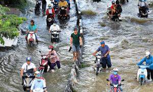 Life goes on as high tide floods Saigon without fail