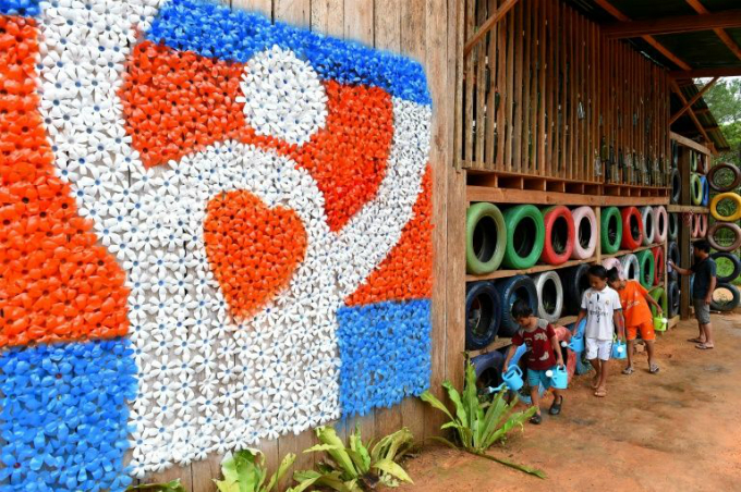 The Coconut School in Cambodia is built almost entirely from waste and features walls made of painted used car tyres.