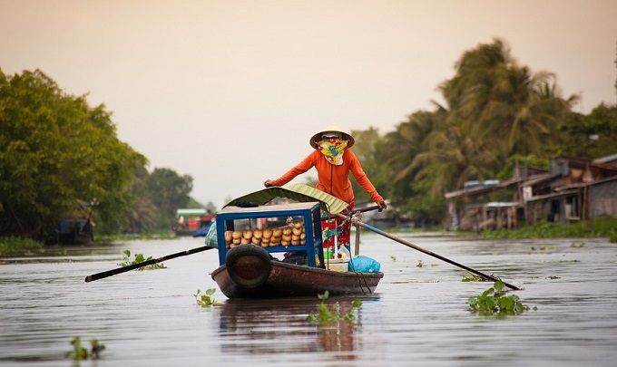 A woman rows a boat in the southern Mekong Delta.