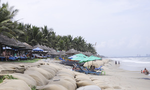 Visitors sunbathe on embankment as erosion ravages central Vietnam beach