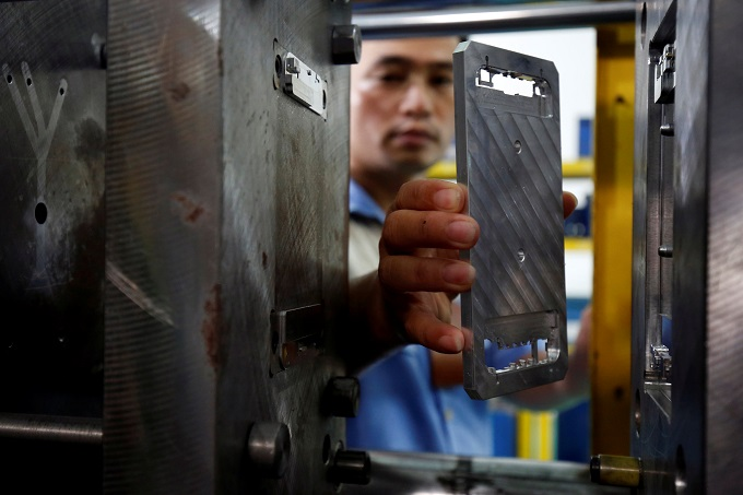A worker holds a metal frame at an assembly plant that produces smartphone in Hanoi, Vietnam, July 5, 2017. Photo by Reuters/Kham