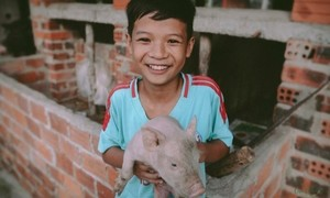 Young Vietnamese boy bears most onerous burdens with a smile