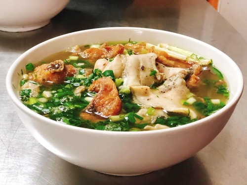 A full bowl of noodle soup, fish cakes and fresh boiled carp.