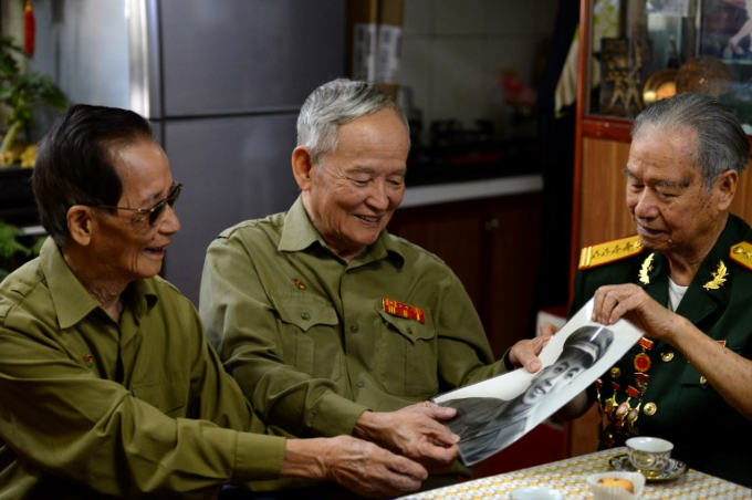 Former Vietnamese soldiers Nguyen Tran Viet (L), Tran Quoc Hanh (C), and Hoang Bao, war veterans of Dien Bien Phu campaign, look at Viets old photograph at his house in Hanoi during an interview with AFP on November 1, 2018. Photo by AFP/Nhac Nguyen