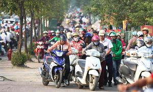 Near downtown Hanoi, residents take their bikes for a walk