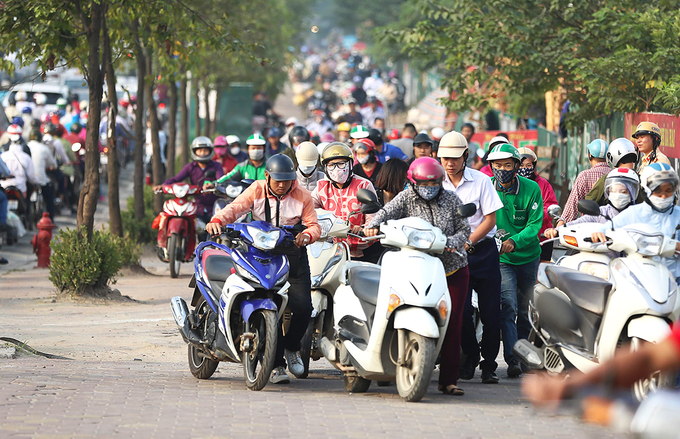Near downtown Hanoi, residents take their bikes for a walk