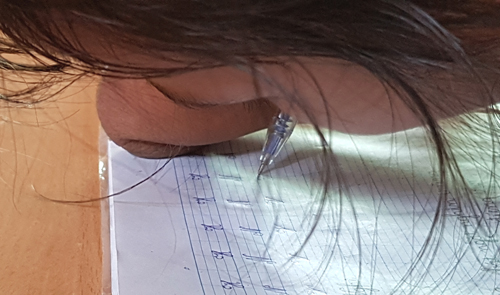 Holding her pen between the stump of her right arm and her face, Thao is able to write as well and as fast as her classmates. Photo by VnExpress/Phuc Hung