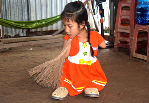 Wielding a big broom between her neck and shoulder, Thao helps her grandmother sweep the houses earthen floor after returning from school. Photo by VnExpress/Phuc Hung