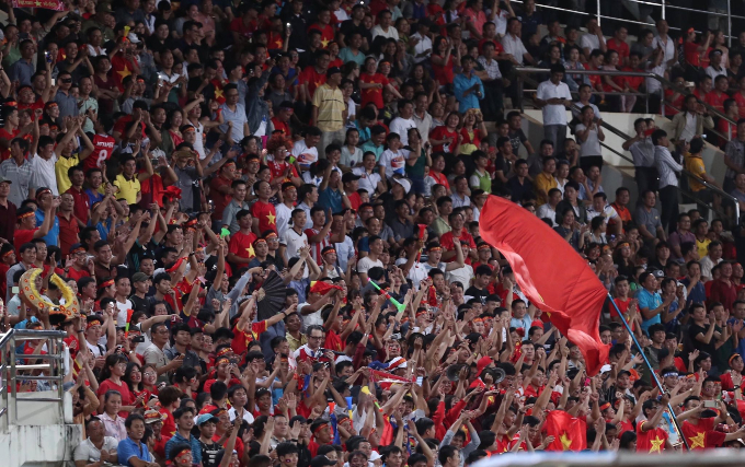 Vietnamese fans cheer at the stadium in Laos.