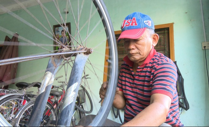 Mai repairs the bike to pay tuition fee. Photo by VnExpress/Thien Ly