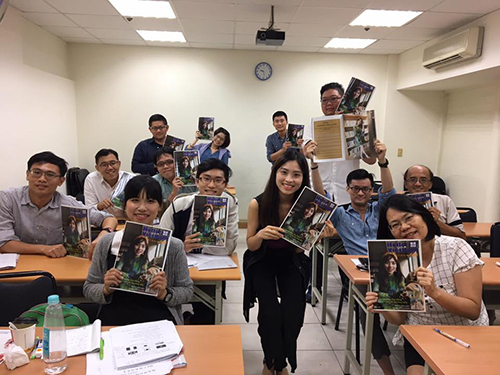 Hang and her students in a Vietnamese class holding a Hello Vietnam Magazine where her face appears on the cover. Photo courtesy of Nguyen Thu Hang