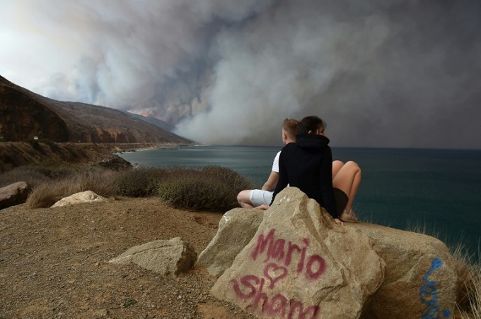 Smoke from the blaze reached toward the ocean along Pacific Coast Highway near Malibu, California. Photo by AFP