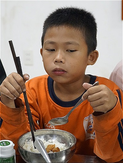 Feeding himself is a major life change for the eight-year-old boy. Photo by VnExpress/Trong Nghia