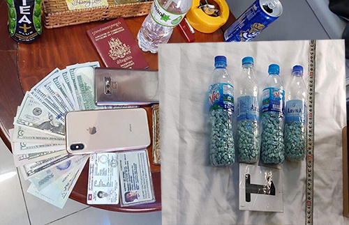 Ecstasy pills and foreign currencies seized by the police as evidence in a Saigon hotel. Photo by VnExpress/Nhat Vy