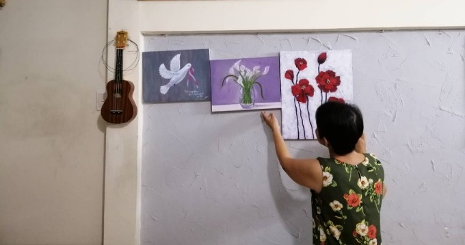 Mai and her paintings at her home. She will give the first one from the left to Tien Nguyen as a present. Mai has been a member at BCNV for three years. Photo by Sen