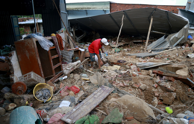 A man searchs for belongings from his collapsed house in Nha Trang. Photo by VnExpress/Xuan Ngoc