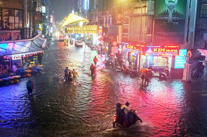 Tourists enjoy heavy downpours, flooding in Saigon